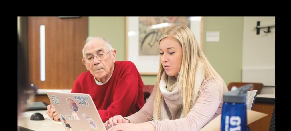 A student sits with a retiree during class